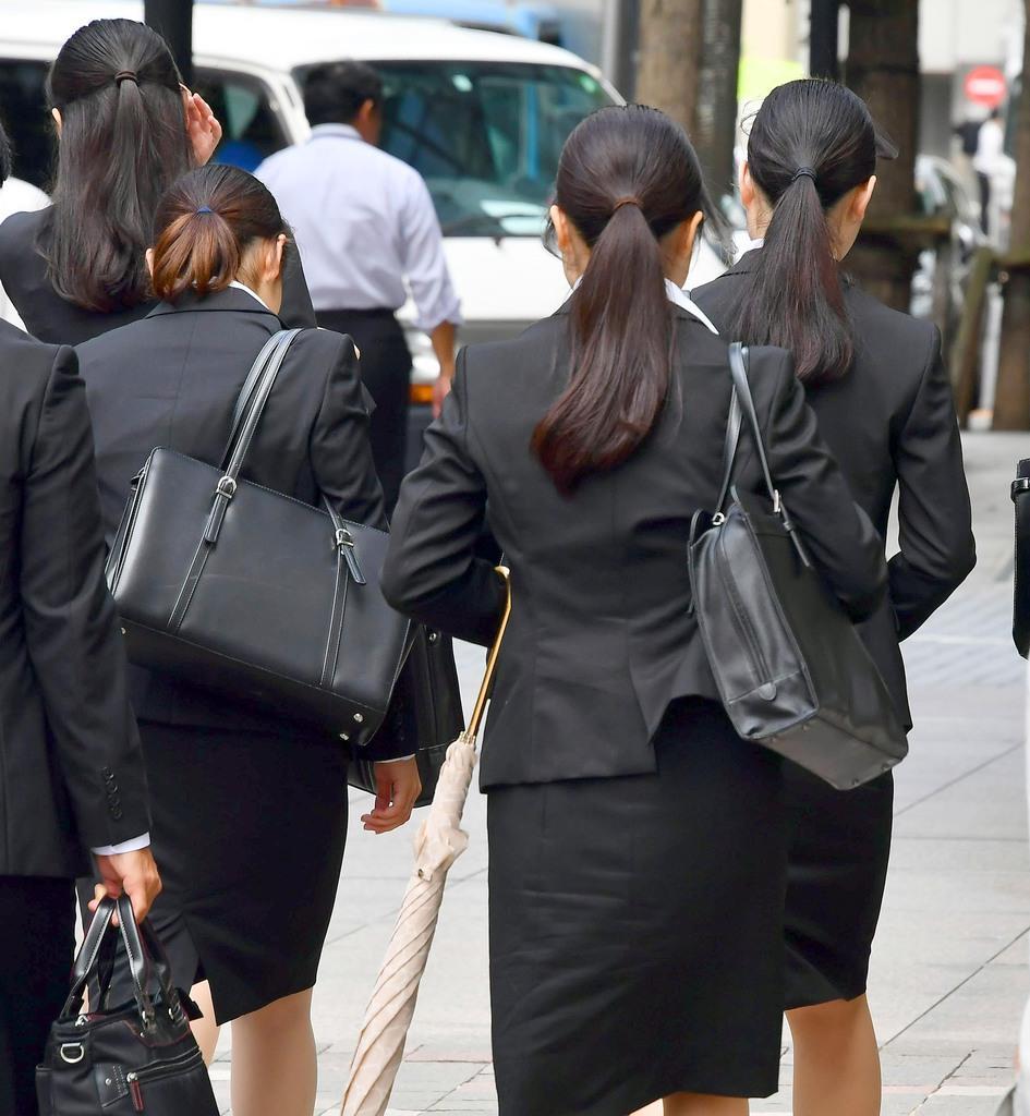 リクルートスーツを着て就職活動する学生たち