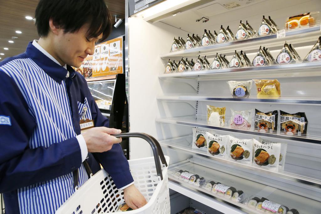 消費期限の近づいた商品を撤去するコンビニの店員=17日午後、東京都品川区