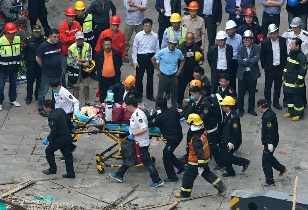 中国上海市のビル倒壊現場で救助活動する消防隊員ら(ロイター)