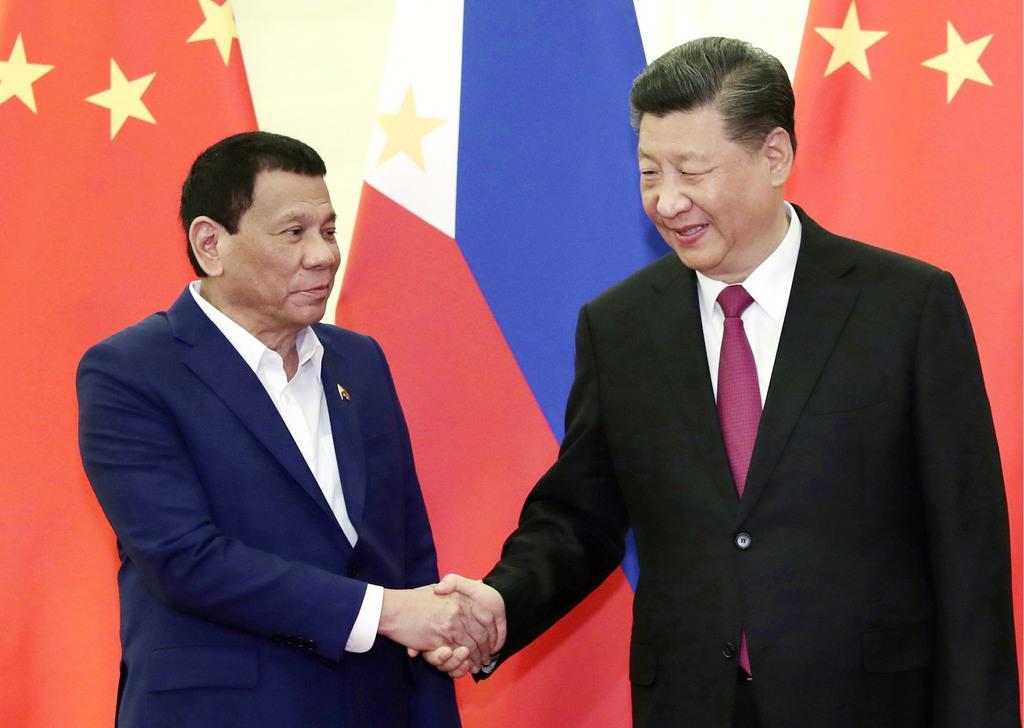会談を前に握手を交わすフィリピンのドゥテルテ大統領(左)と中国の習近平国家主席=4月25日、北京の人民大会堂(共同)