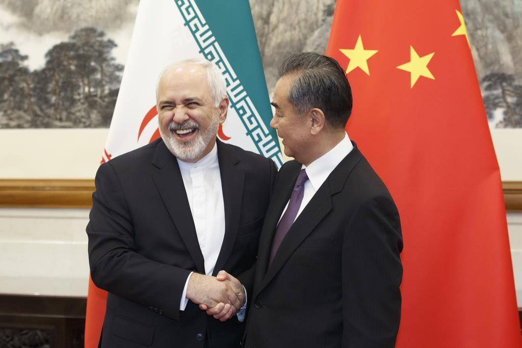 訪中し、王毅国務委員兼外相と握手するイランのザリフ外相(AP)