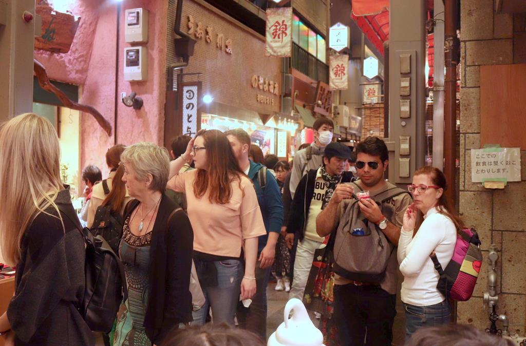 外国人を中心に店前などで食べ歩く観光客が多い=京都市中京区の錦市場