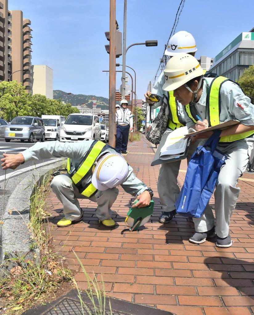 歩道の縁石に不備がないかを確認する県職員=16日、大津市