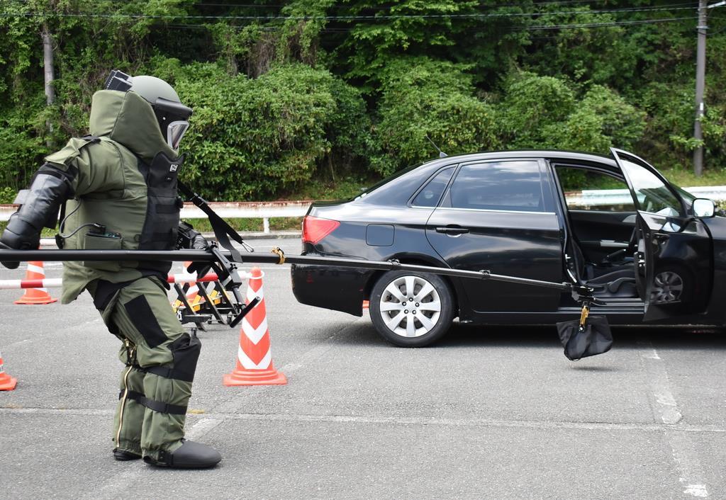 テロ対処訓練で、車内から爆発物に見立てたかばんを取り出す県警機動隊員=生駒市
