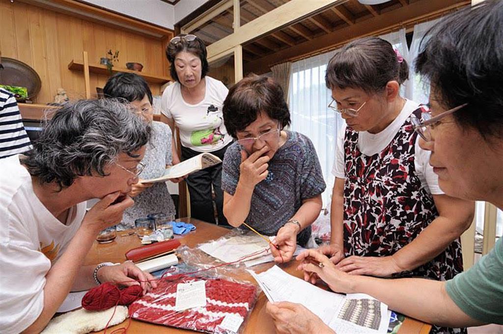 図面を前に編み物指導を受けるアミマーさん(ハートニットプロジェクト撮影)