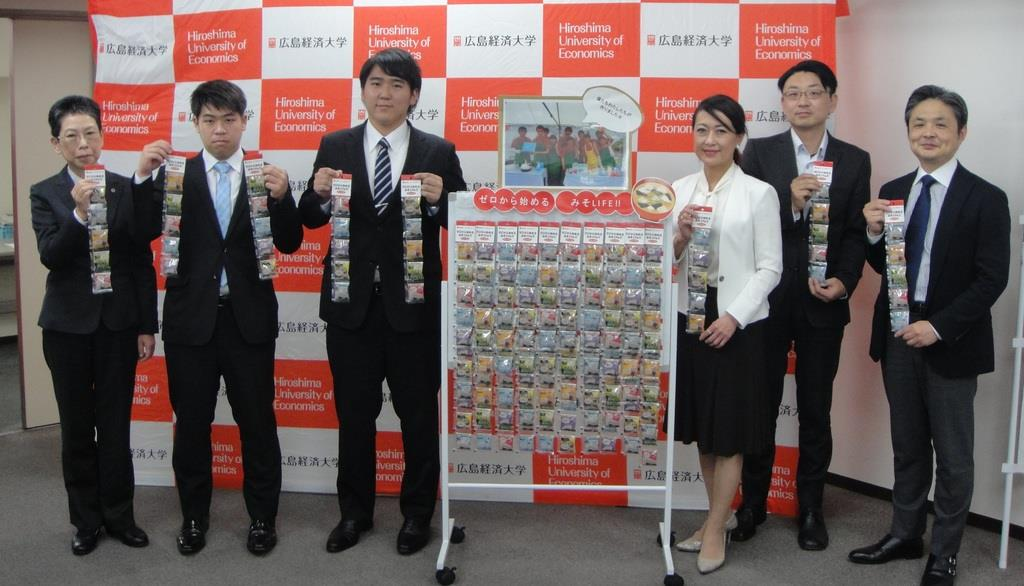 広島経済大の学生らと共同開発した新商品を披露する新庄みその山本美香社長(右から3人目)ら=広島市西区