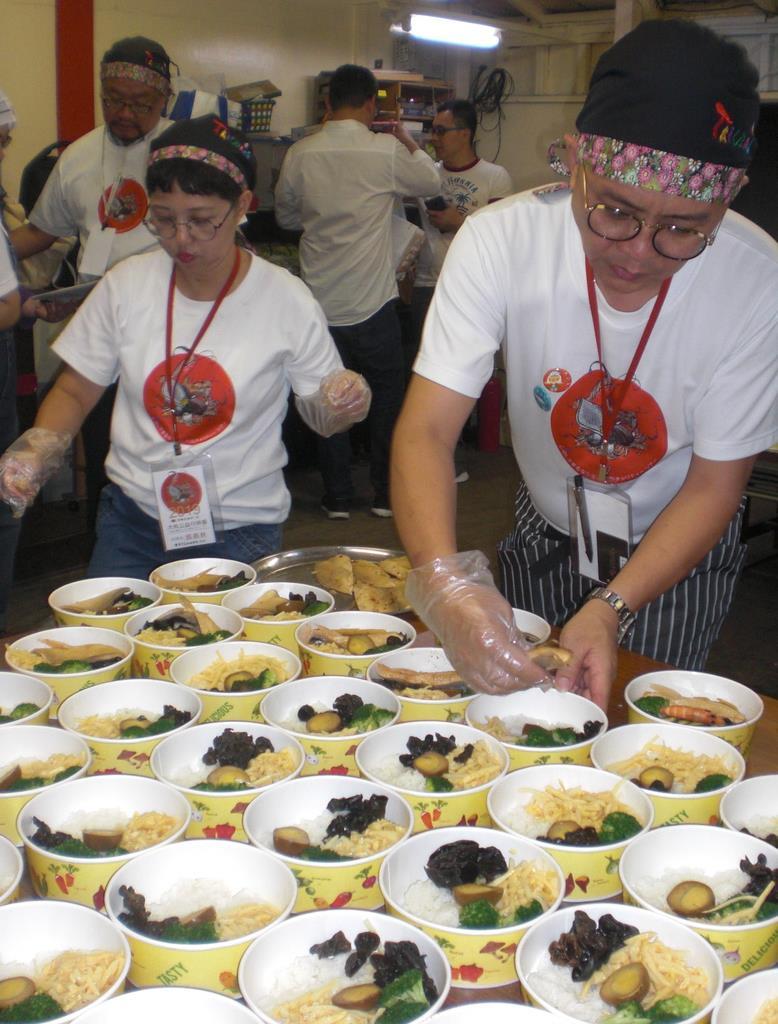 炊き出しのための料理を準備する蔡瑞成さん(右)らボランティアのメンバー=大阪市西成区