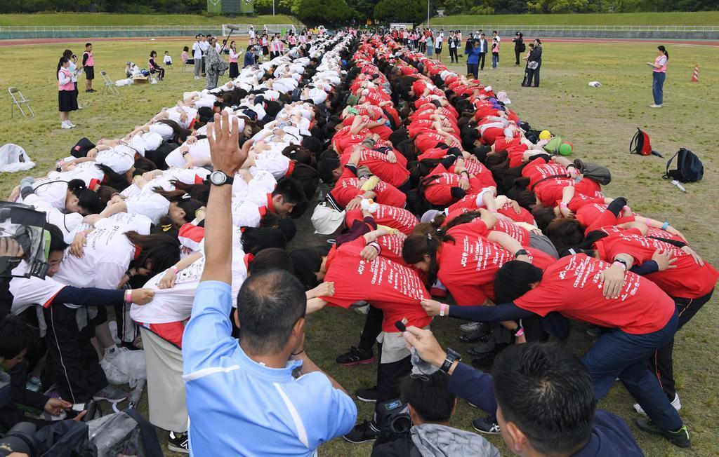 ラグビーW杯日本大会を盛り上げるイベントで、「大スクラム」を組む市民ら=18日午後、福岡市
