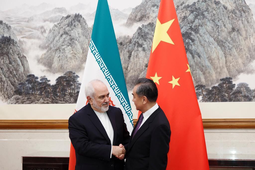 17日、北京で王毅国務委員兼外相(右)と握手するイランのザリフ外相(ロイター)