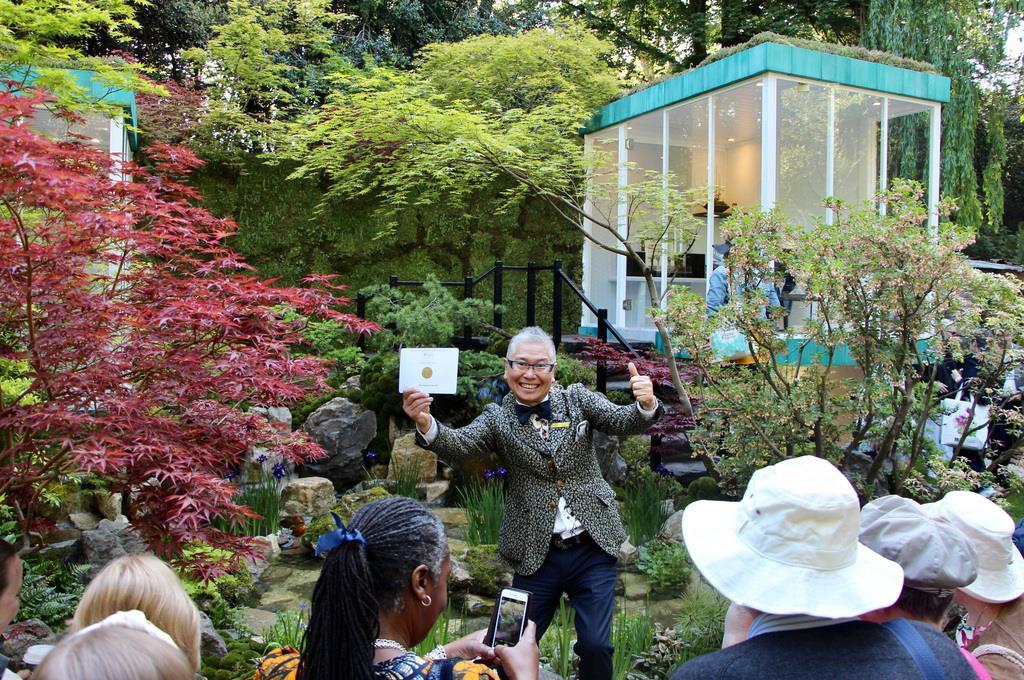 獲得した金メダルを手に自身の手掛けた庭の前でポーズをとる石原和幸さん=21日、ロンドン(栗本洋撮影)
