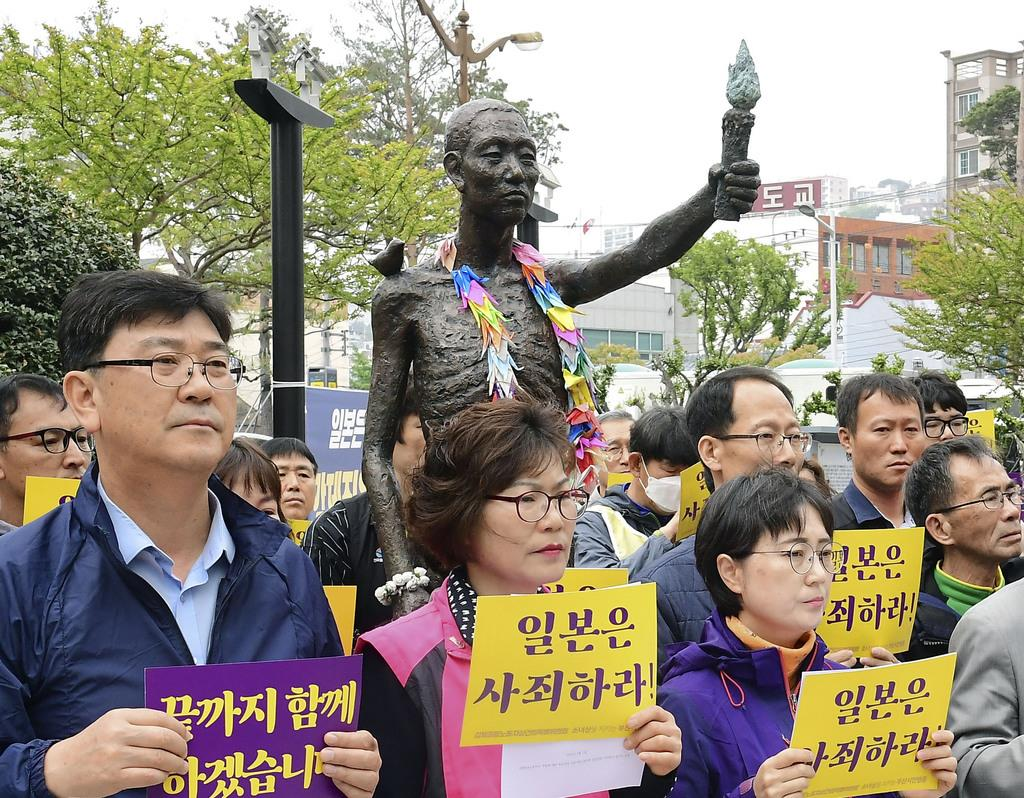 徴用工像の周辺で行われた集会の参加者=1日、韓国・釜山(共同)