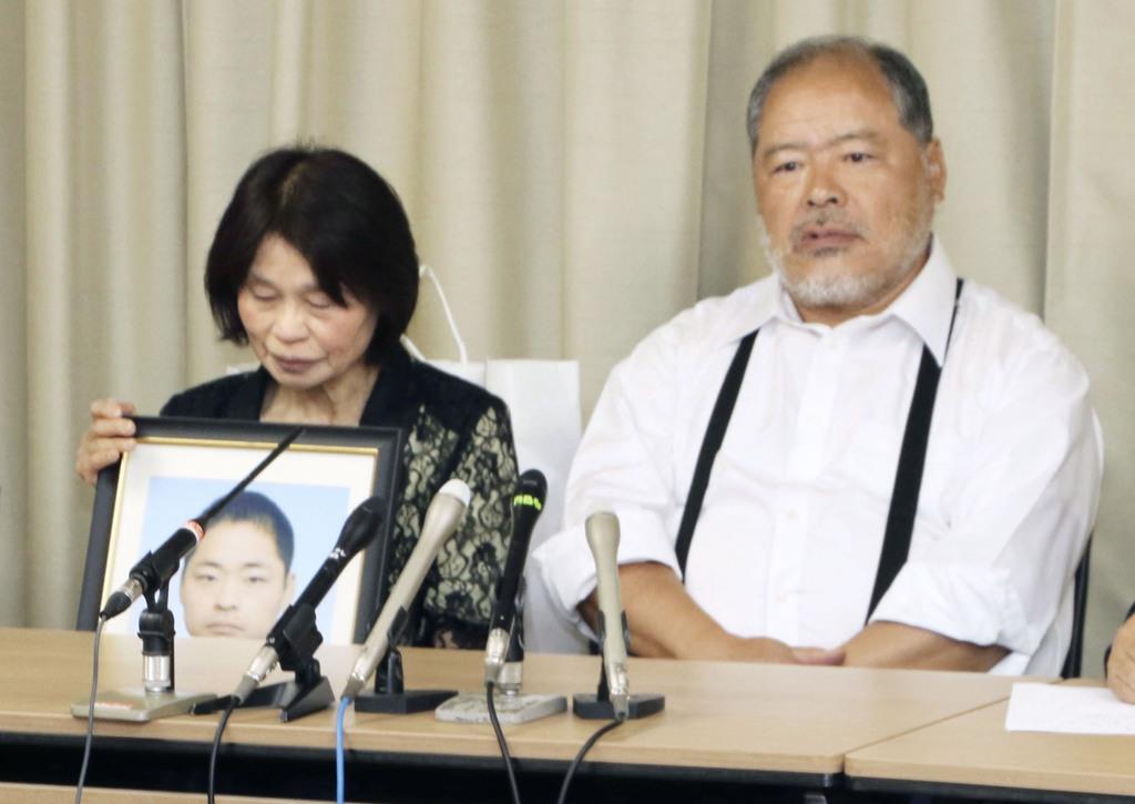 自殺した西田幹さんの遺影を前に、記者会見する両親=24日午前、奈良市