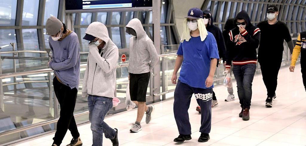 日本へ移送するため、タイの空港に到着した特殊詐欺に関与したとみられる日本人の男ら=24日、バンコク郊外(共同)