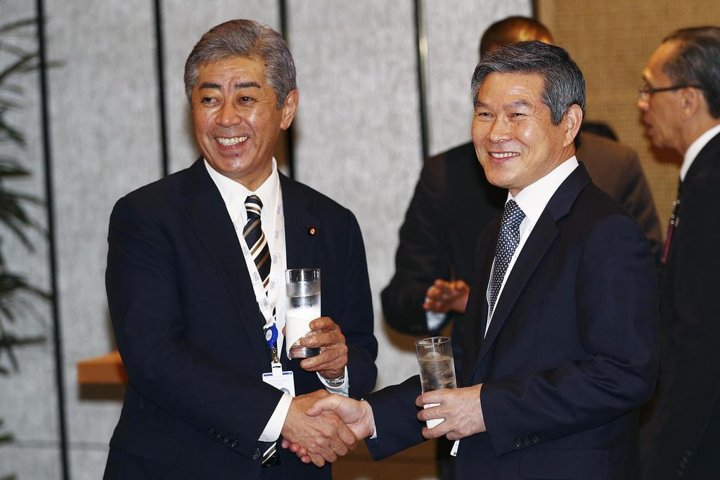 「アジア安全保障会議」の昼食会で握手する岩屋防衛相(右)と韓国の鄭景斗国防相(左)=1日、シンガポール(AP)