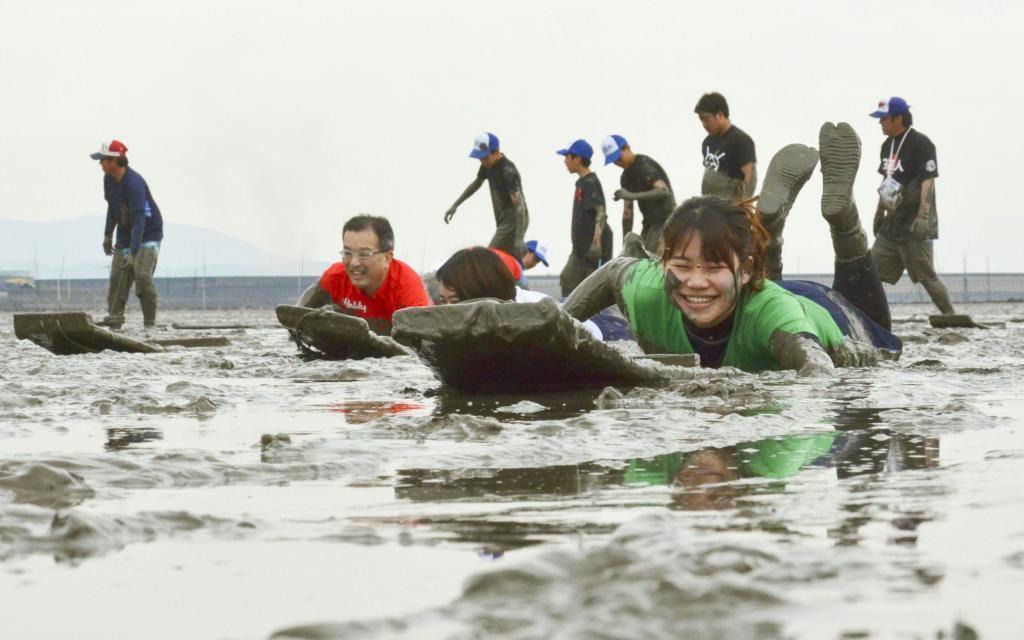 泥まみれになりながら「鹿島ガタリンピック」を楽しむ参加者=佐賀県鹿島市