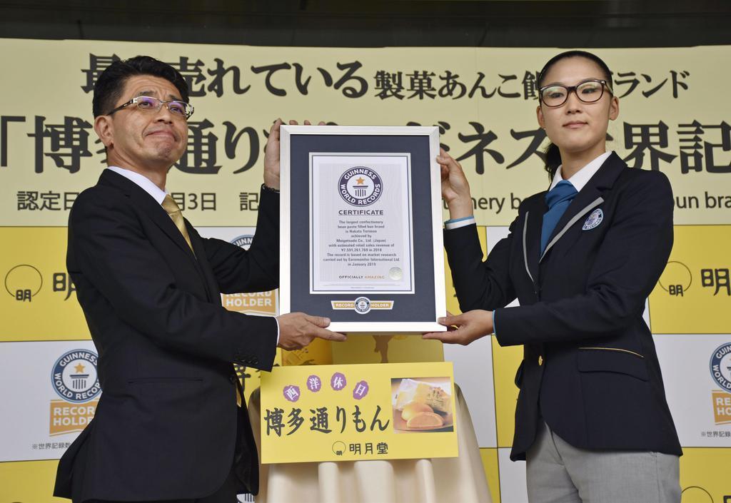 「博多通りもん」がギネス世界記録の認定を受け、認定証を掲げる明月堂の秋丸真一郎社長(左)=3日午前、福岡市
