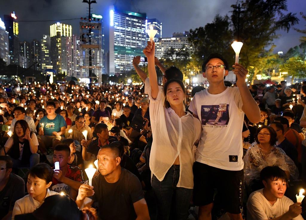 天安門事件から30年を迎え、ろうそくを手に犠牲者を悼む人たち=4日、香港のビクトリア公園(共同)