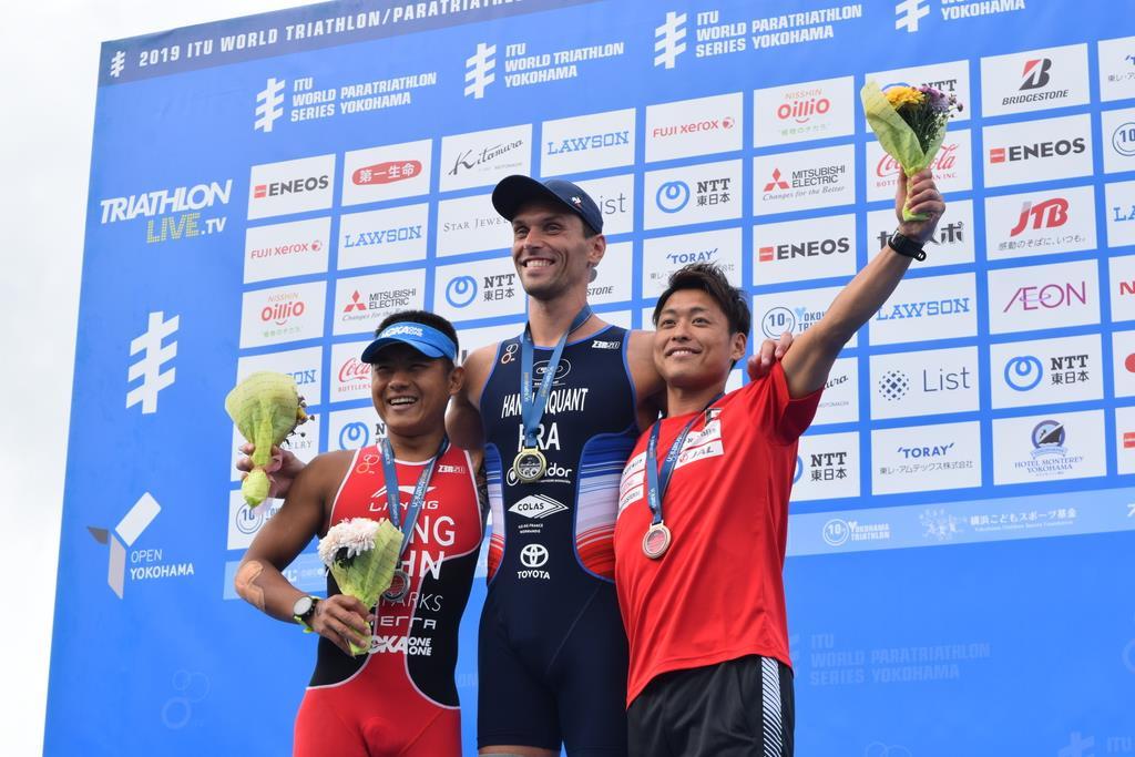 表彰台で他国の選手と喜びを分かち合う宇田秀生選手(右)