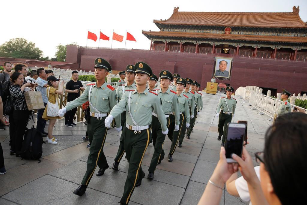 観光客がカメラを向ける中、北京の天安門広場を行進する中国の治安部隊(5月16日、ロイター)