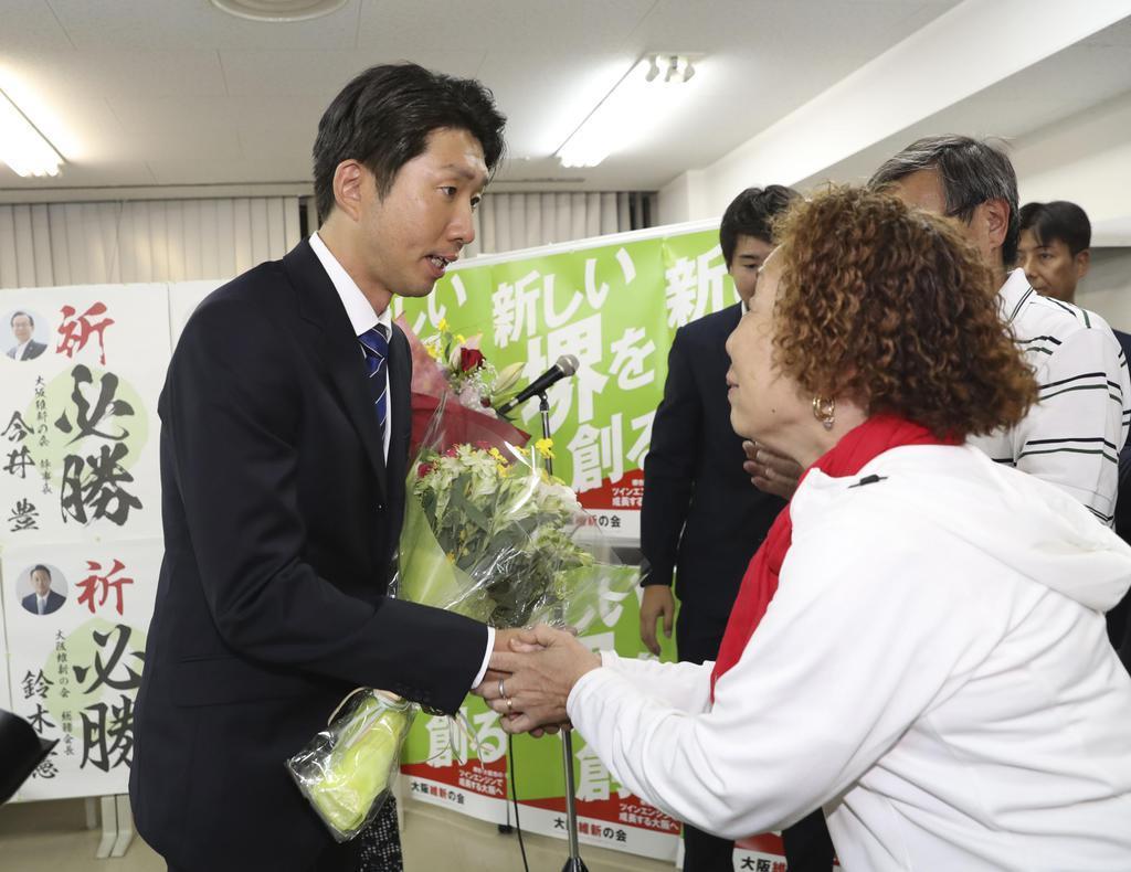 堺市長選で初当選を決め、花束を受け取る大阪維新の会の永藤英機氏(左)=9日夜、堺市