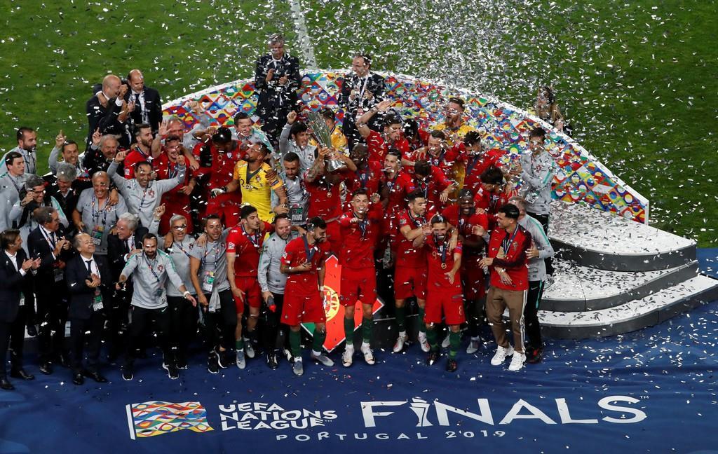 サッカーの欧州ネーションズリーグで優勝トロフィーを掲げ、勝利を祝うポルトガル代表=9日、ポルト(ロイター)