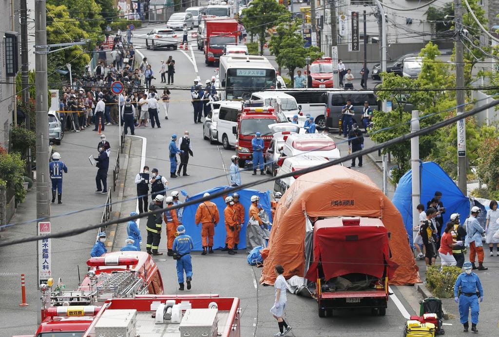 小学生を含む複数の人が刺された現場で救助活動をする消防隊員ら。中央上は通学バス=5月28日午前9時28分、川崎市多摩区