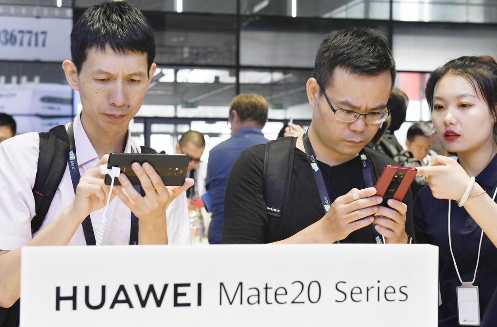 「CESアジア」のファーウェイのブースで、スマートフォンを手に取る人たち=11日、中国上海市(共同)