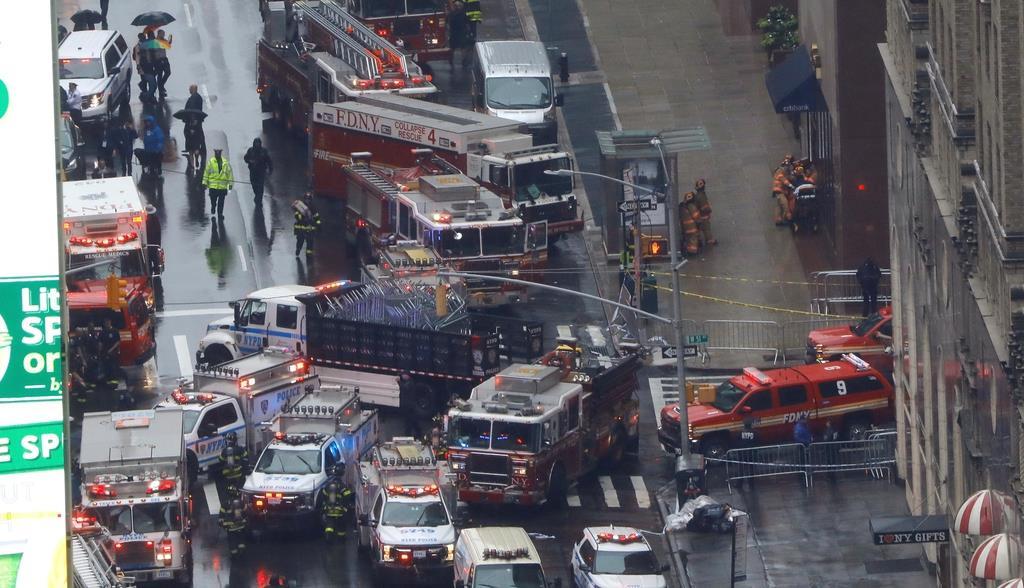 ヘリコプターが不時着した高層ビルの下に集まった緊急車両=10日、ニューヨーク(ロイター)