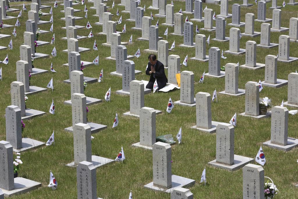 6日、韓国ソウルの国立顕忠院で、朝鮮戦争で亡くなった親族の墓に祈りを捧げる男性(AP)
