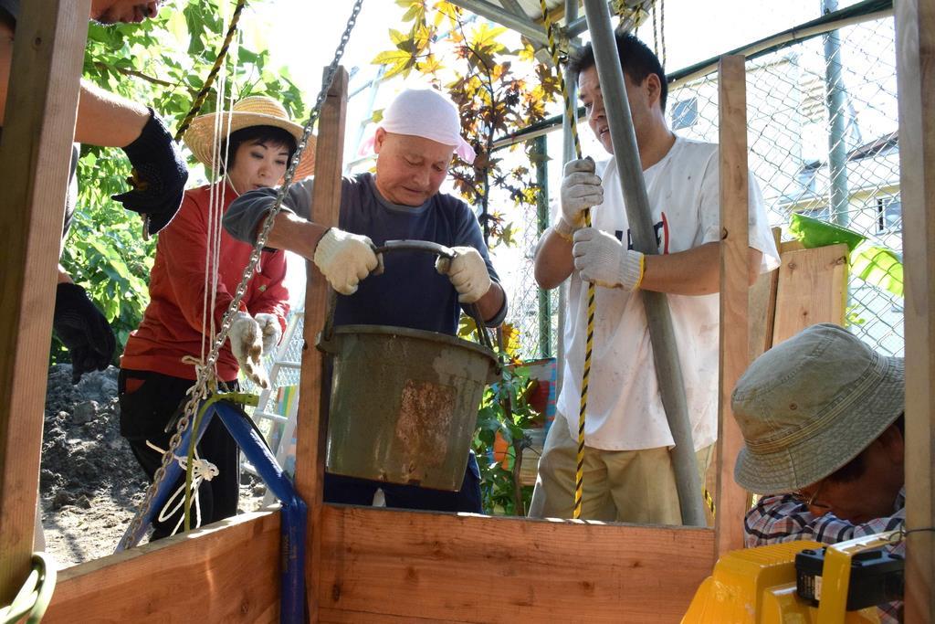 掘削中の井戸からバケツで泥水をくみだす参加者ら=大阪市西成区