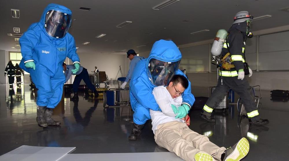 テロによる爆発現場から放射線が検出された想定で、防護服を着た隊員による負傷者の救出訓練が行われた=12日、成田空港(城之内和義撮影)
