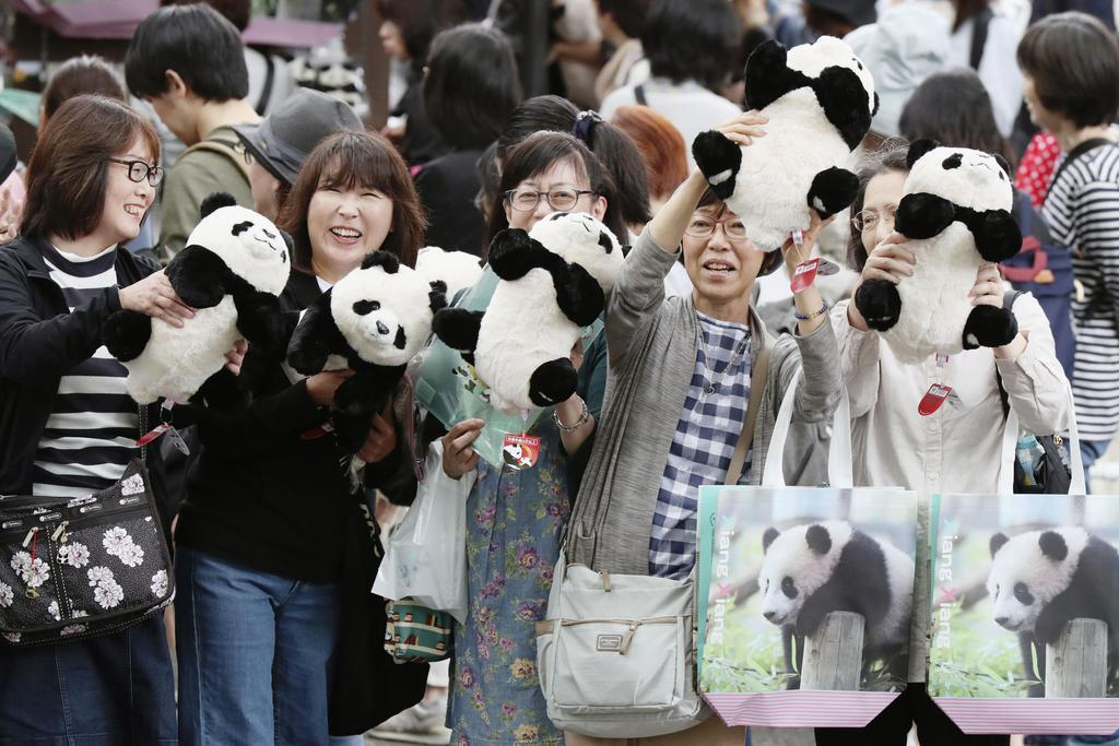 シャンシャンが2歳を迎えた東京・上野動物園で、縫いぐるみを手に笑顔を見せる人たち=12日午後