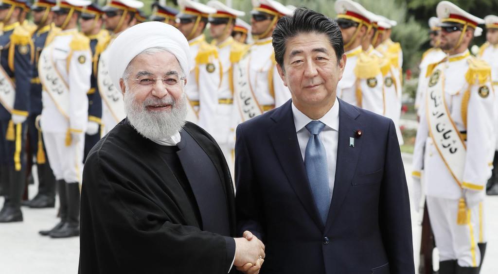 歓迎式典でイランのロウハニ大統領(左)と握手する安倍首相=12日、テヘラン(共同)