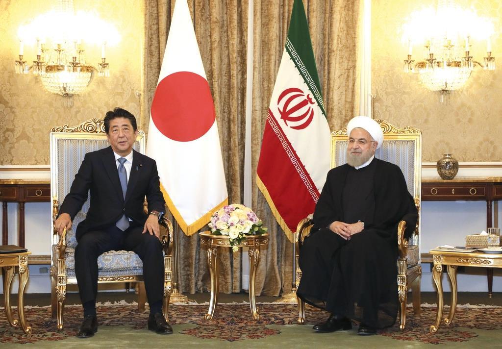 イランのロウハニ大統領(右)と会談する安倍首相=12日、テヘラン(代表撮影・共同)