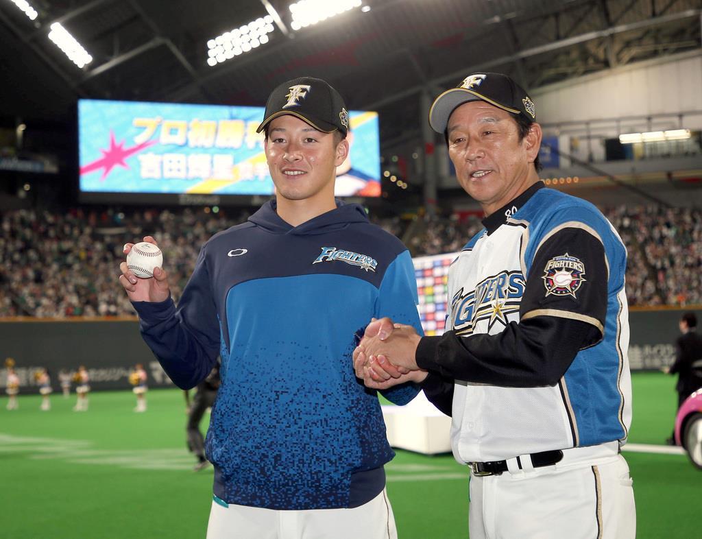 初先発初勝利をあげ、栗山監督(右)から祝福される日本ハム・吉田輝=札幌ドーム(撮影・荒木孝雄)