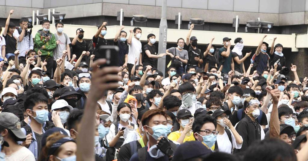 「逃亡犯条例」改正案の撤回を求め、立法会前に集まった若者ら=12日、香港(共同)