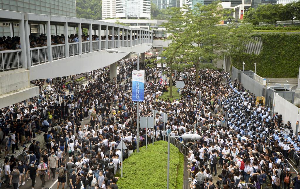 「逃亡犯条例」改正案の撤回を求め、立法会(右側)前に集まった人たち=12日、香港(共同)