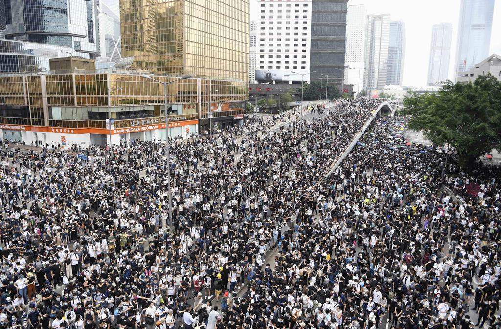 「逃亡犯条例」改正案の撤回を求め、立法会周辺の道路を埋める人たち=12日、香港(共同)