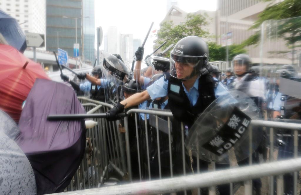 「逃亡犯条例」改正案の撤回を求めて集結し、警官隊に棒で打ち付けられる人たち=12日、香港の立法会周辺(ロイター)