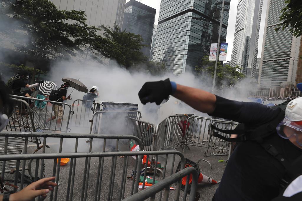「逃亡犯条例」改正案の撤回を求めて集結し、催涙弾を浴びた人たち=12日、香港の立法会周辺(AP)