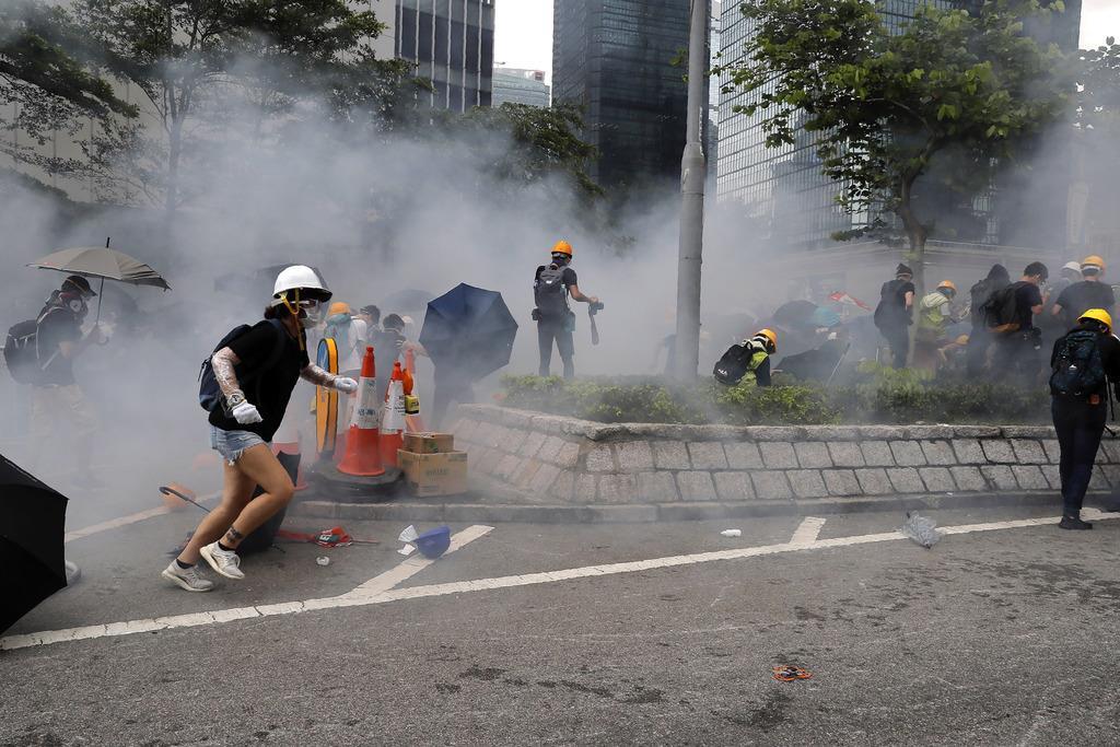 警官隊から催涙弾を放たれ、逃げ惑う人たち=12日、香港の立法会周辺(AP)