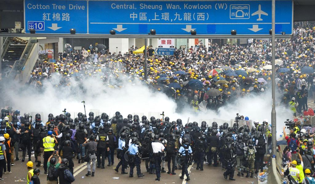 催涙弾の白煙が上がる中、立法会周辺の道路でデモ隊(奥)と対峙(たいじ)する警官隊=12日、香港(共同)