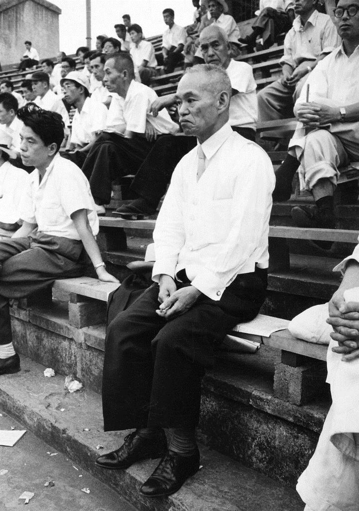 学生野球をスタンドで観戦する世耕弘一氏=中央、近畿大学提供