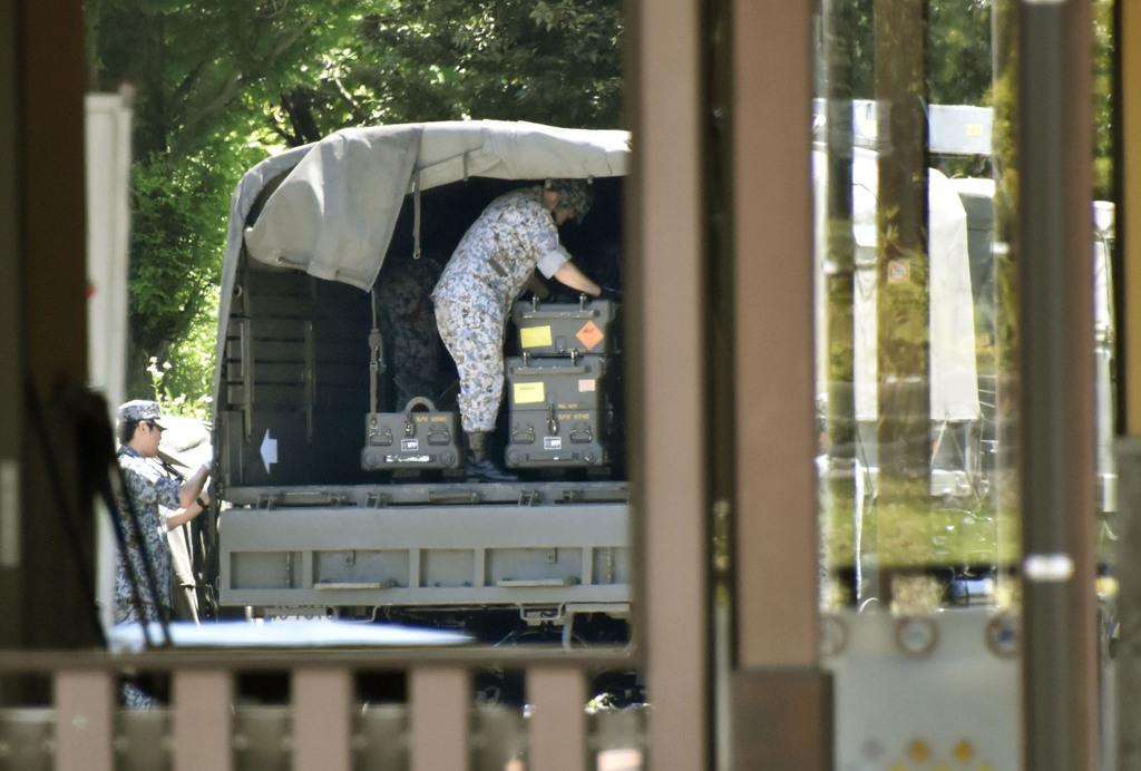 栃木県壬生町の壬生パーキングエリアで車両の積み荷を整える自衛隊員=13日午後0時44分