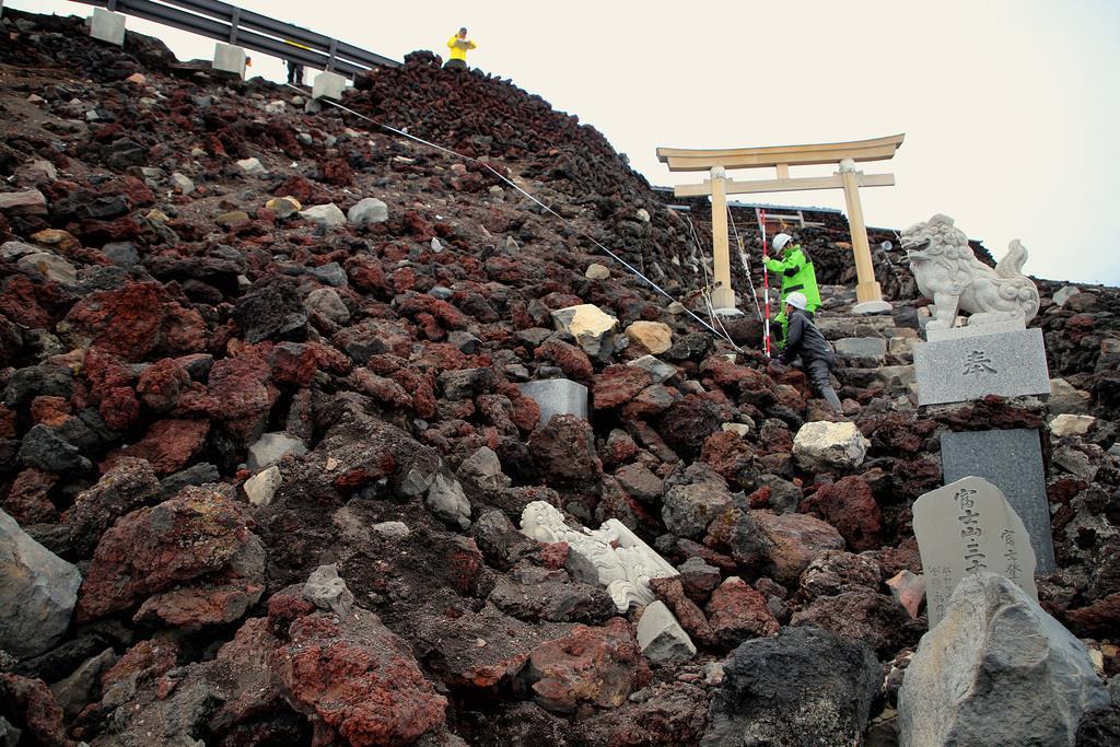 富士山・吉田ルートの山頂付近の石積み崩落現場を調べる関係者=4日、富士山(早坂洋祐撮影)