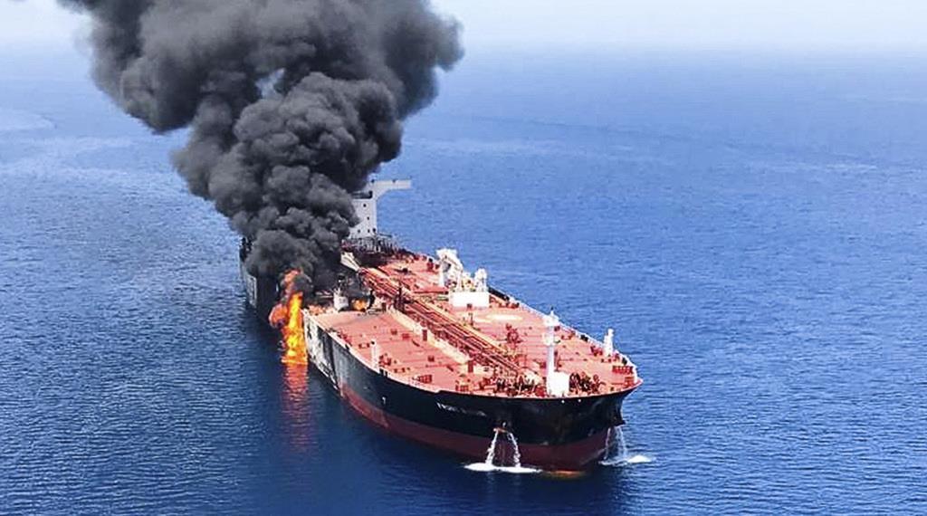 13日、ホルムズ海峡付近で攻撃を受けて火災を起こし、オマーン湾で煙を上げるタンカー(AP)