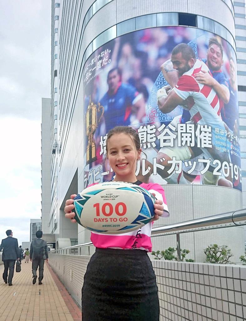 大型プレー写真を背に、100日前記念ボールを手にする開催都市特別サポーターのドーキンズ英里奈さん=JR大宮駅西口近く(岡田浩明撮影)