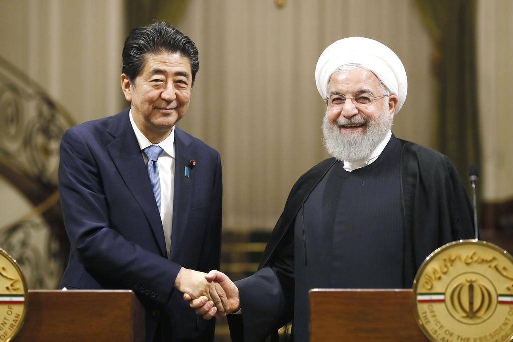 共同記者発表を終え、握手するイランのロウハニ大統領(右)と安倍首相=12日、テヘラン(共同)