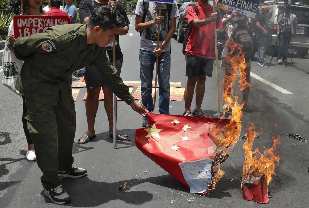 12日、フィリピンの首都マニラで、中国の五星紅旗を燃やす人たち(AP)