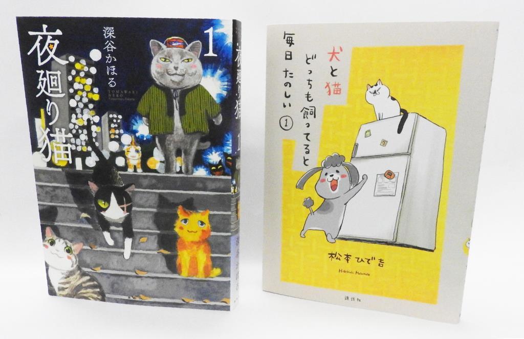さりげない人間の行動に猫がエールを送る深谷かほるさん作の漫画『夜廻り猫』(講談社)と、犬、猫と暮らす作者が日常を描いた松本ひで吉さん作『犬と猫どっちも飼ってると毎日たのしい』(講談社)